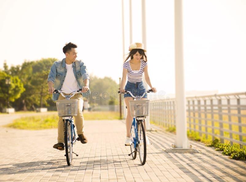 Молодое катание пар на велосипеде в парке города стоковые изображения rf