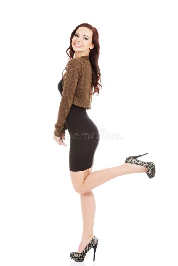 Молодое красивое в черном платье и коричневой куртке болеро. стоковое фото