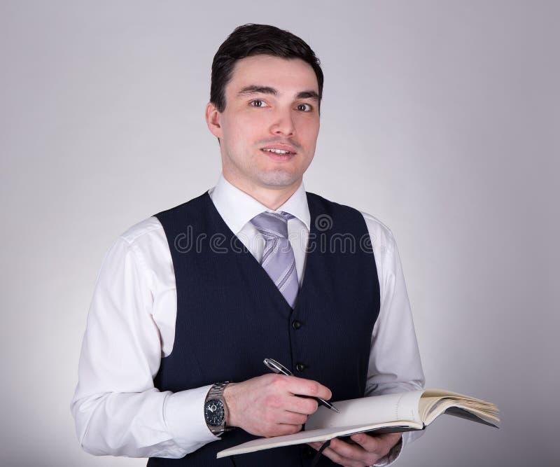 Молодое красивое сочинительство бизнесмена что-то в блокноте над gr стоковые фото