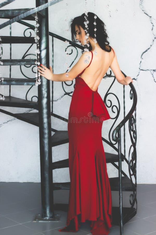 Молодое модельное брюнет в красный представлять платья стоковая фотография rf