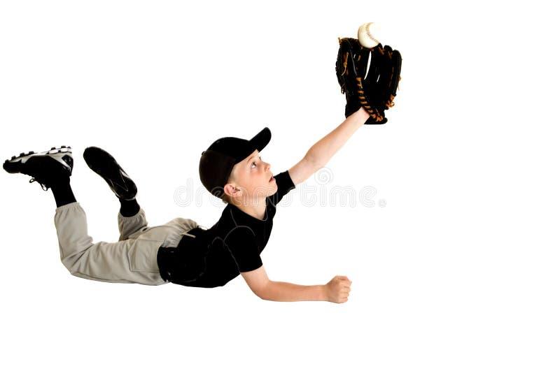Молодое подныривание бейсболиста для того чтобы уловить шарик мухы стоковые изображения