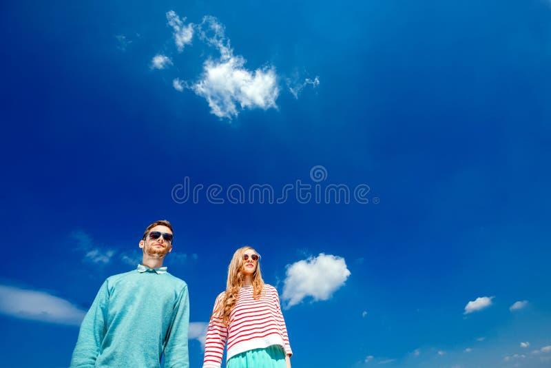 Молодое положение пар и уверенно смотрит вперед на голубом c стоковое фото rf
