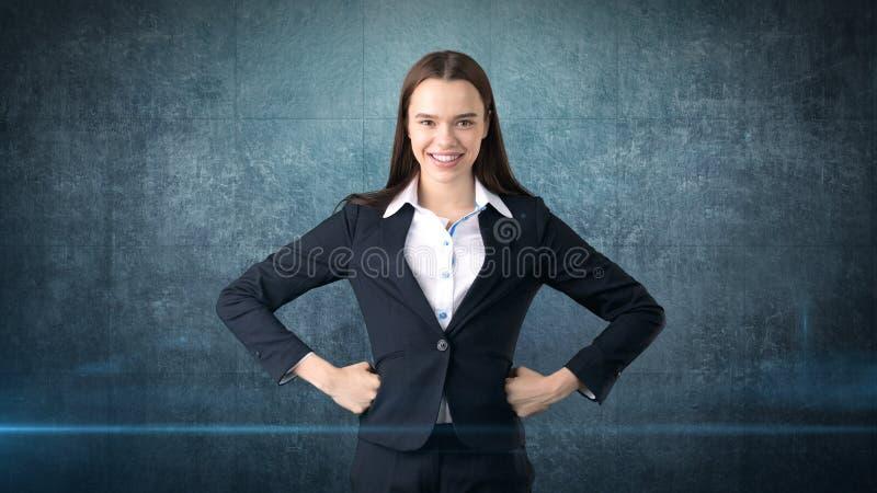 Молодое платье бизнес-леди в черном костюме и белой рубашке стоять, держа ее руки на бедрах с copyspace стоковое фото rf