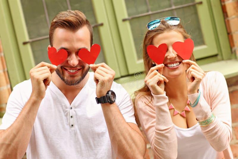 Молодое романтичное заволакивание пар наблюдает с сердцами в городе стоковое фото rf