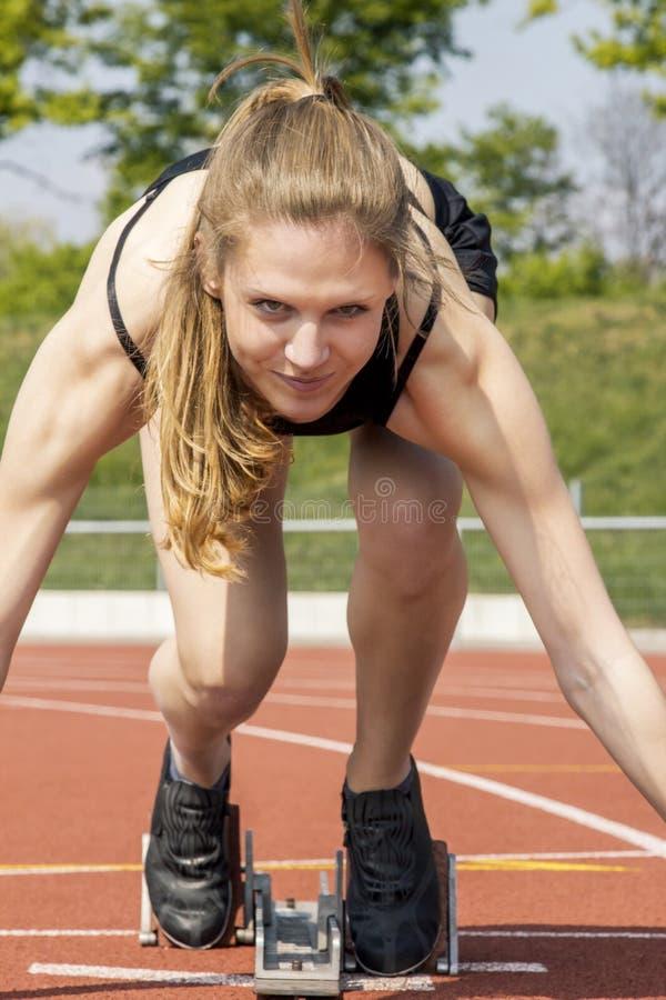 Молодое стартовое положение спортсменки стоковое фото rf