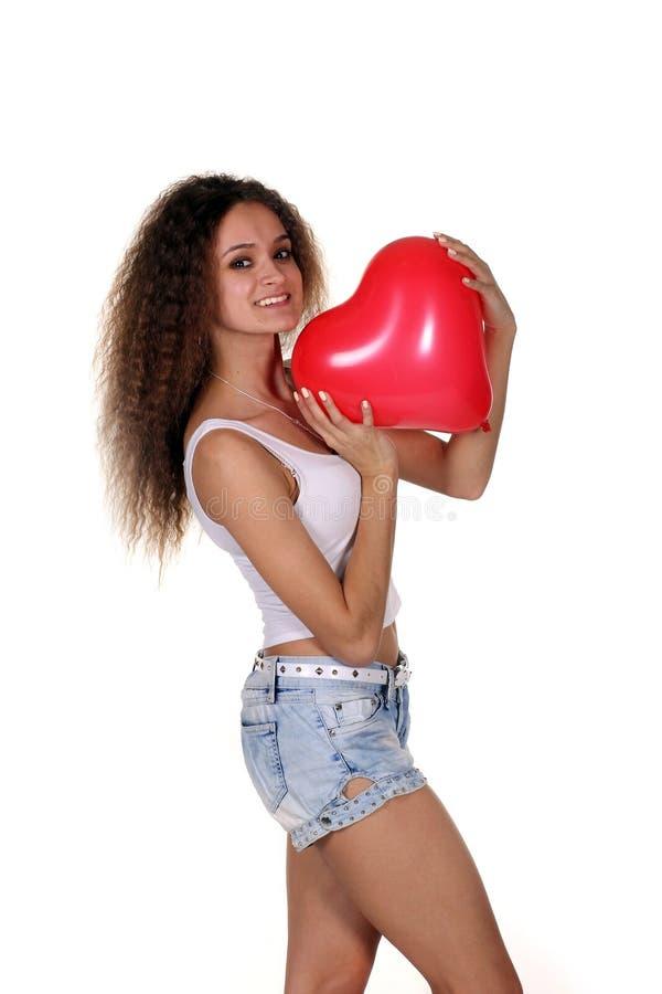 Молодое счастливое сердце красного цвета владением женщины стоковое изображение