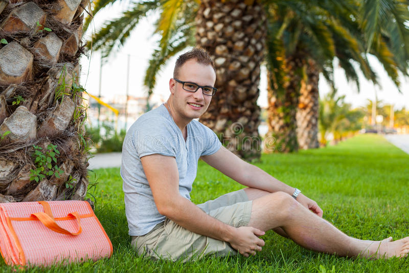 Молодое туристское усаживание под пальмой модель способа взволнованности представляя положительную древесину сугроба Vacatio стоковое фото