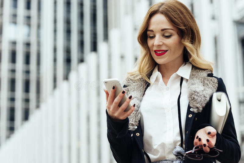 Молодое умное чтение профессиональной женщины используя телефон стоковая фотография