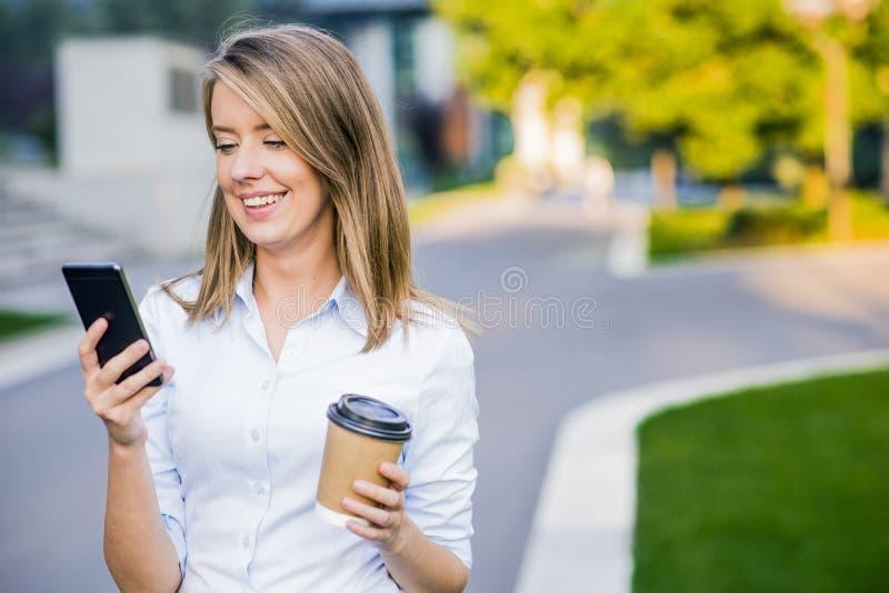 Молодое умное чтение профессиональной женщины используя телефон Женские новости чтения коммерсантки или отправляя СМС sms на smar стоковые фотографии rf