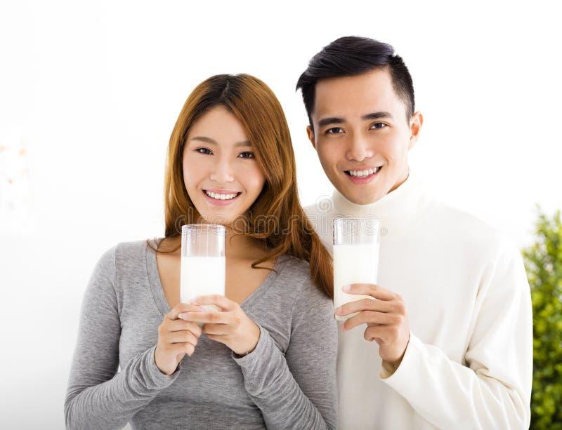 Молодое усмехаясь питьевое молоко пар стоковое фото rf