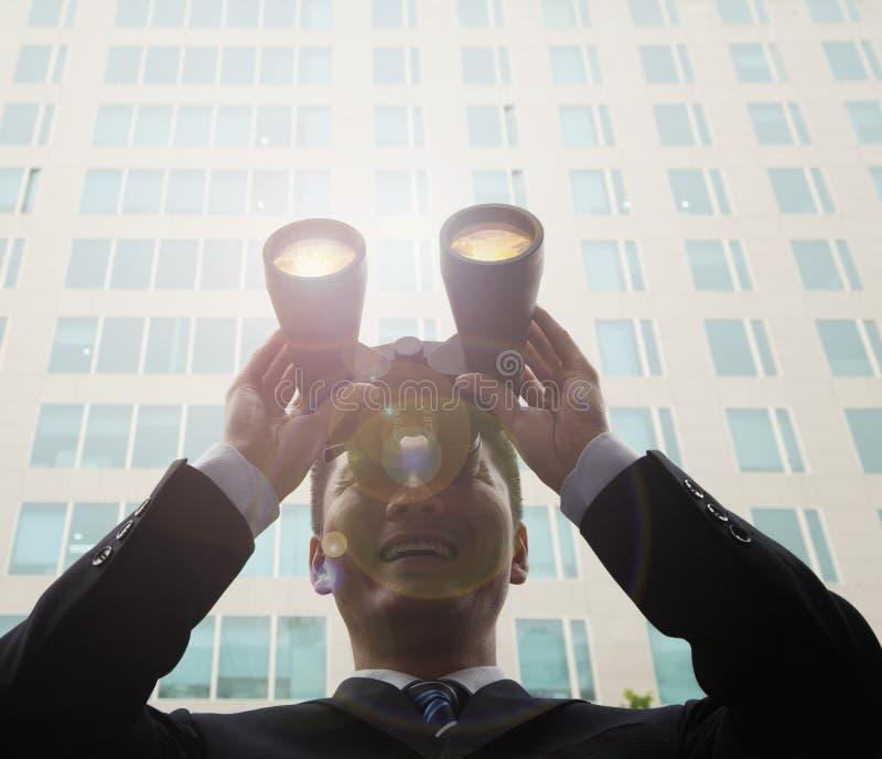 Молодое, усмехаясь снаружи бизнесмена стоящее небоскреба и смотреть через бинокли с пирофакелом в Пекине, Китаем объектива стоковые изображения rf