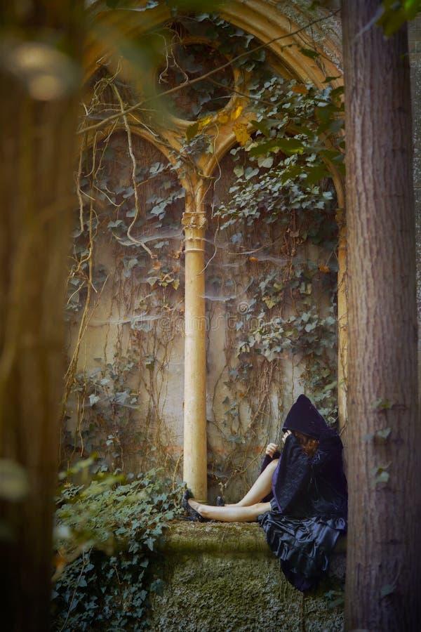 Молодое goth при клобук представляя сидеть стоковые изображения