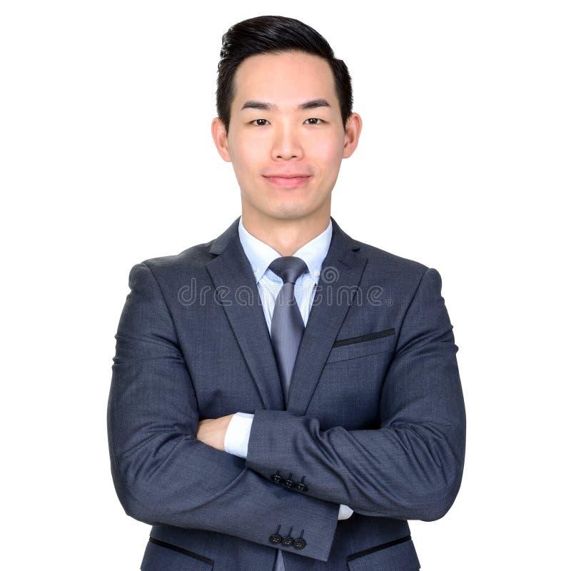 Молодой азиатский бизнесмен пересекая его оружия стоковая фотография