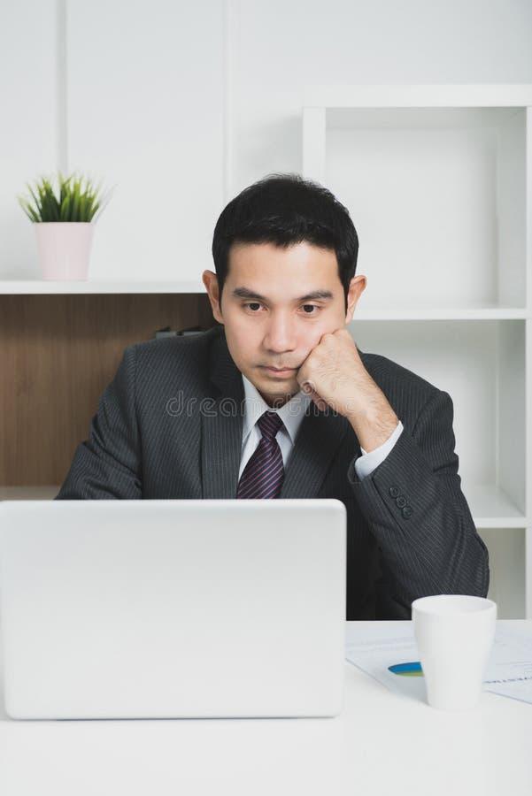 Молодой азиатский бизнесмен смотря портативный компьютер стоковая фотография rf