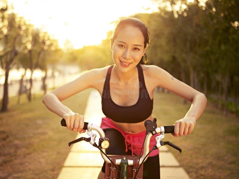 Молодой азиатский велосипед катания женщины outdoors на заходе солнца стоковое фото rf