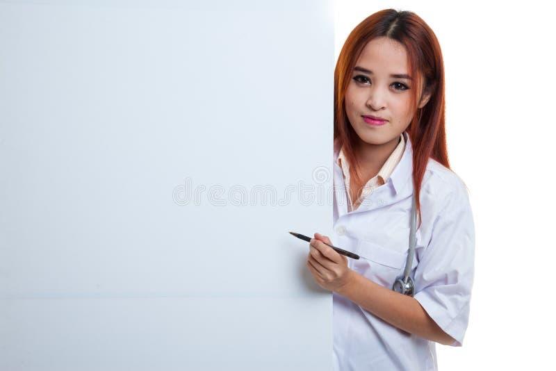 Молодой азиатский женский доктор peeking от заднего пустого пункта w знака стоковая фотография rf