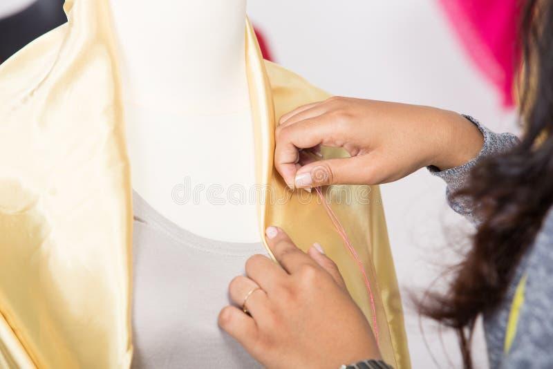 Молодой азиатский дизайнер прикалывая fabrice на манекене, конец вверх стоковые изображения