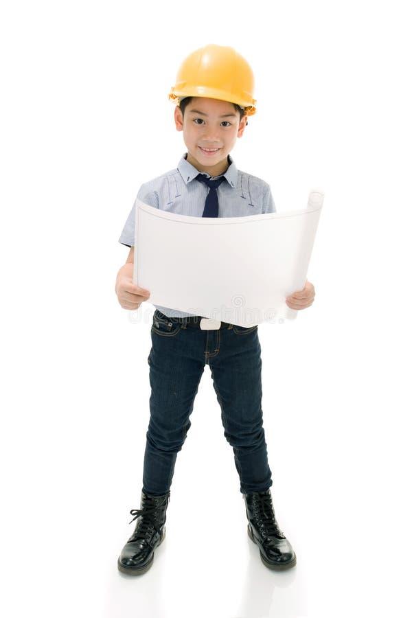 Молодой азиатский инженер по строительству и монтажу ребенка держа оборудование стоковая фотография