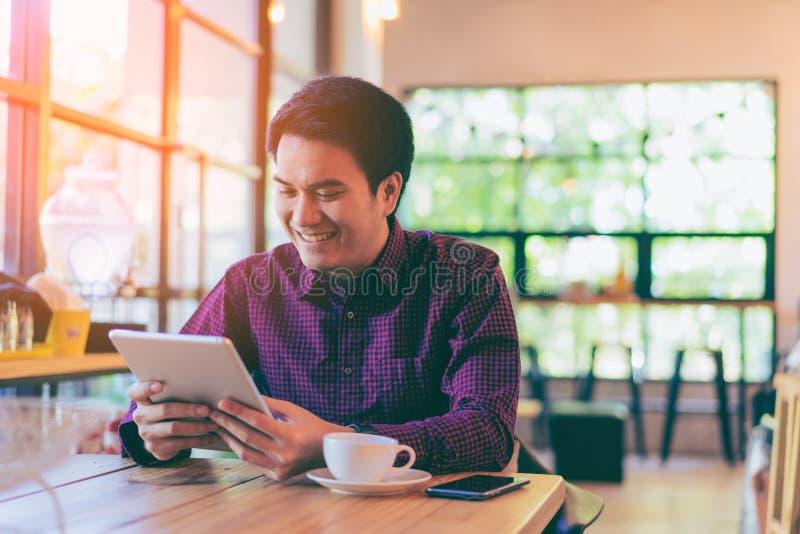 Молодой азиатский красивый бизнесмен усмехаясь пока читающ его таблицу стоковое изображение