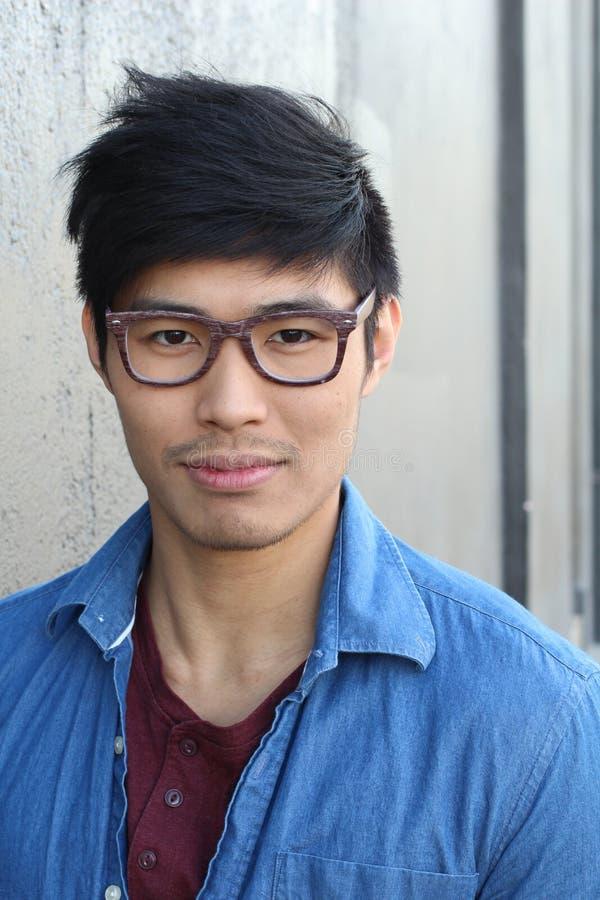 Молодой азиатский мужчина с усмехаться стекел стоковая фотография rf