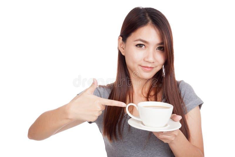 Молодой азиатский пункт женщины к чашке кофе стоковое фото