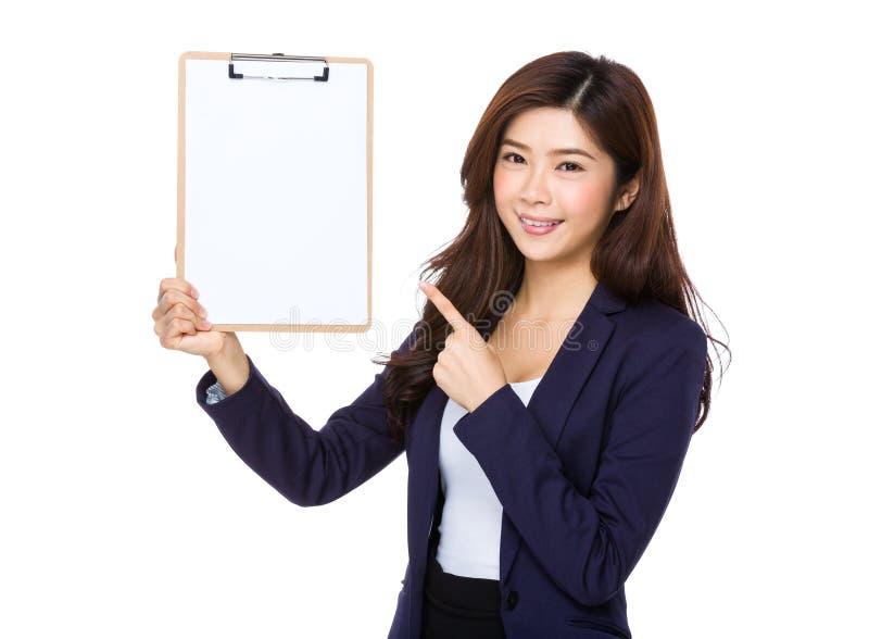 Молодой азиатский пункт коммерсантки для того чтобы прикрыть доску сзажимом для бумаги стоковое изображение rf
