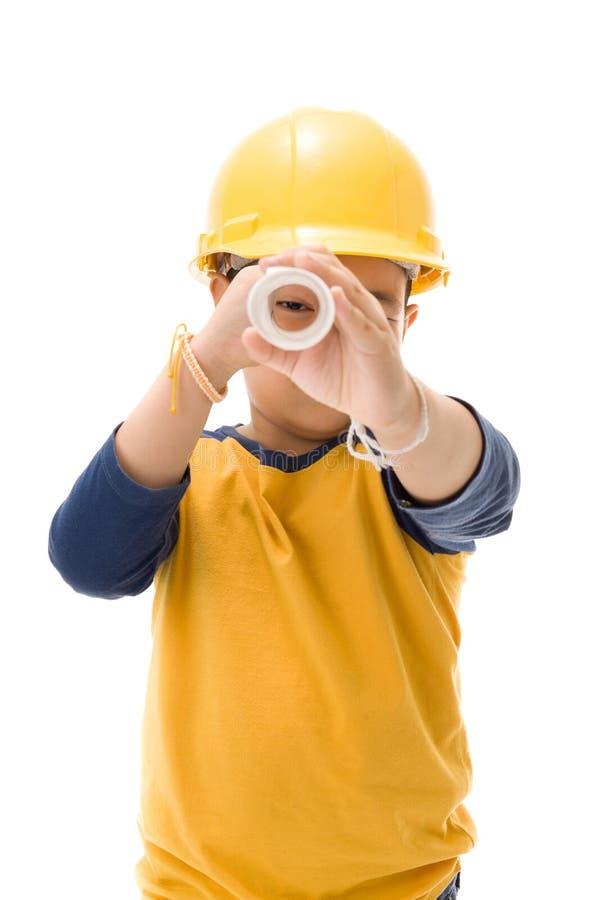 Молодой азиатский рабочий-строитель ребенка держа оборудование стоковое изображение