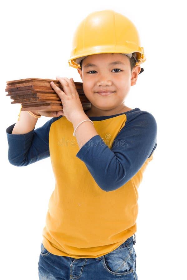Молодой азиатский рабочий-строитель ребенка держа оборудование стоковое фото