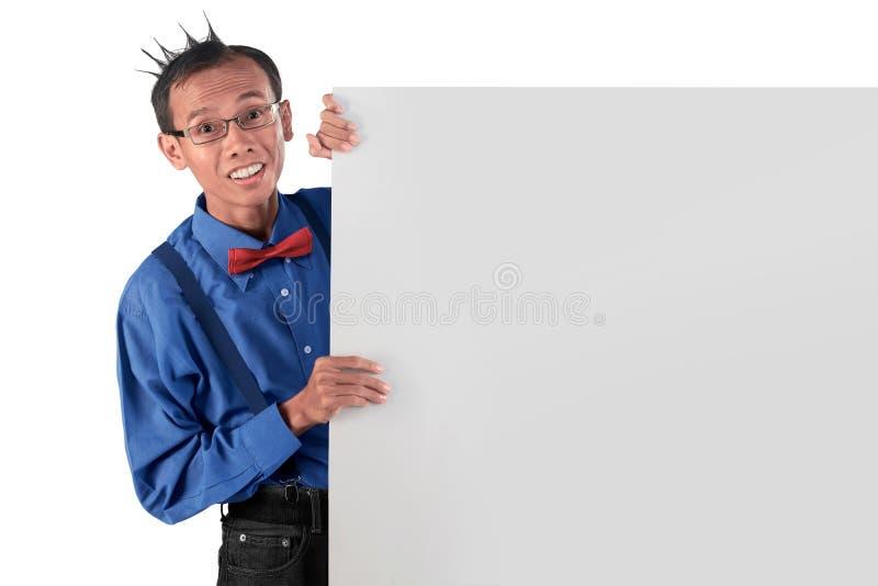 Молодой азиатский смешной человек стоя за пустой доской для copyspace стоковое фото rf
