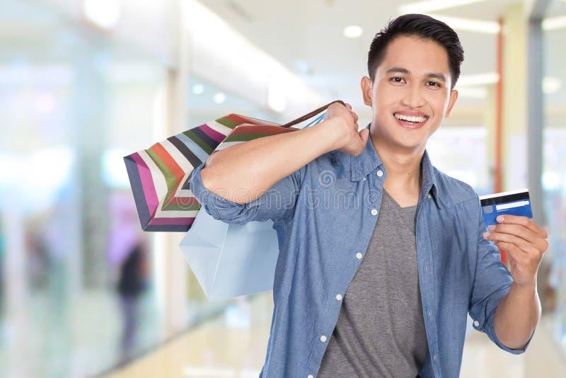 Молодой азиатский человек держа хозяйственные сумки и кредитную карточку, конец вверх стоковое фото