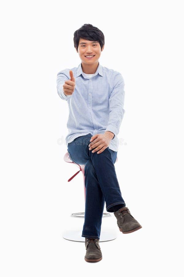 Молодой азиатский человек показывая большой палец руки. стоковая фотография rf