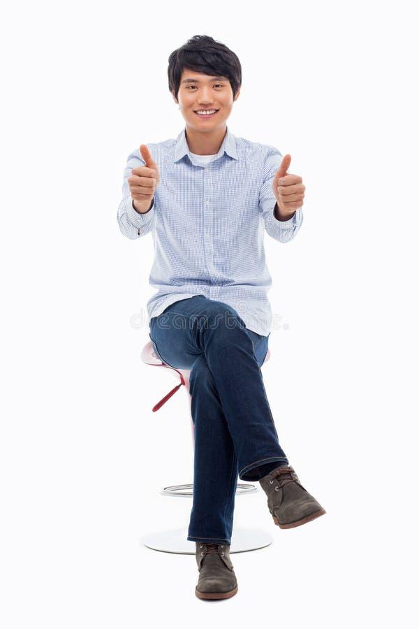 Молодой азиатский человек показывая большой палец руки. стоковые фото