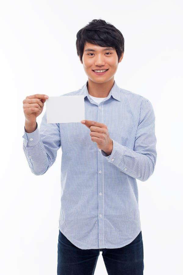 Молодой азиатский человек показывая пустую карточку. стоковое изображение rf