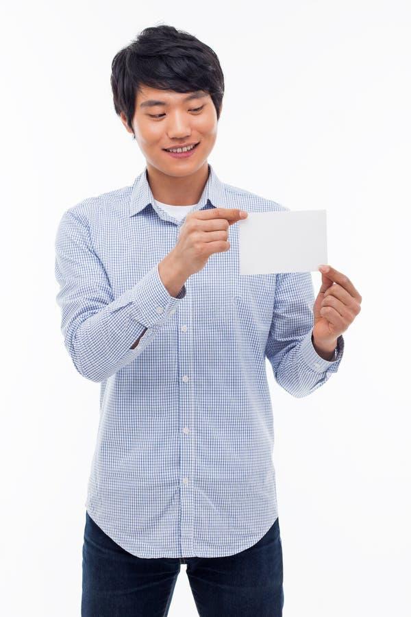 Молодой азиатский человек показывая пустую карточку. стоковые изображения rf