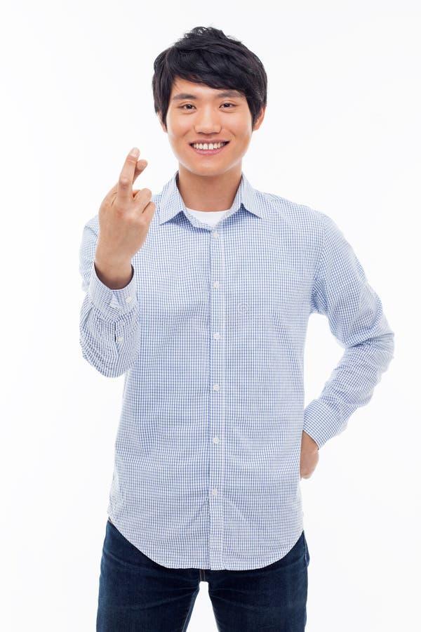 Молодой азиатский человек показывая удачливейший знак. стоковая фотография