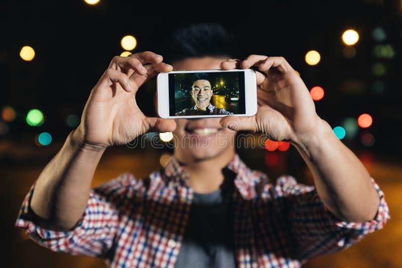 Молодой азиатский человек принимая selfie в городе стоковые фото