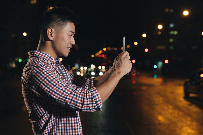 Молодой азиатский человек при наушники фотографируя стоковые изображения rf