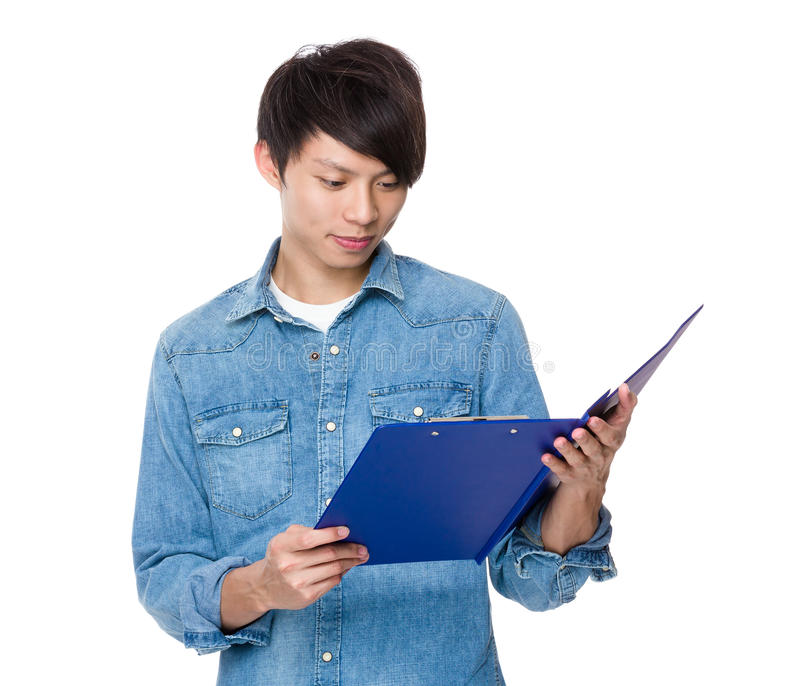 Молодой азиатский человек прочитанный на доске сзажимом для бумаги стоковые изображения rf