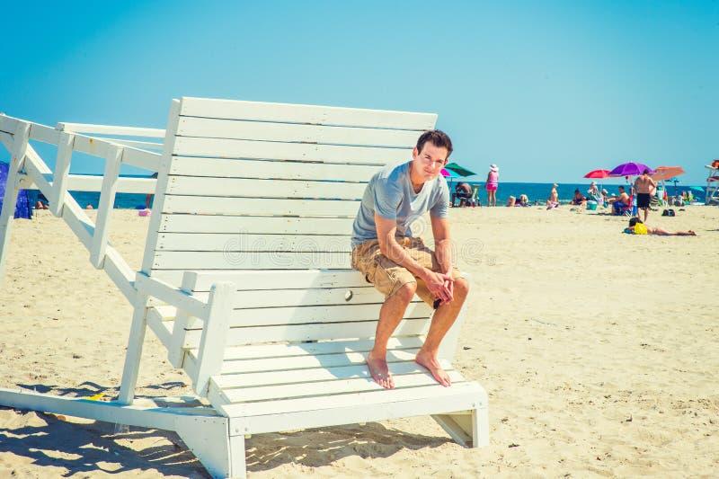 Молодой американский путешествовать человека, ослабляя на пляже в новом Jerse стоковые изображения rf
