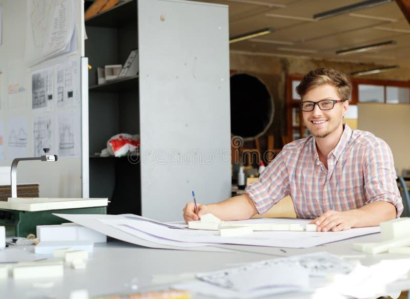 Молодой архитектор работая на чертежном столе в студии архитектора стоковые изображения rf