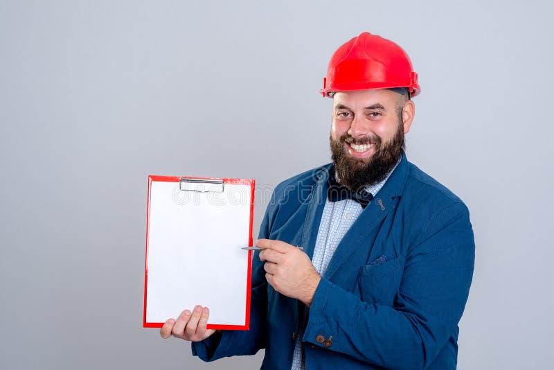 Молодой архитектор с красными шлемом и доской сзажимом для бумаги стоковые фотографии rf