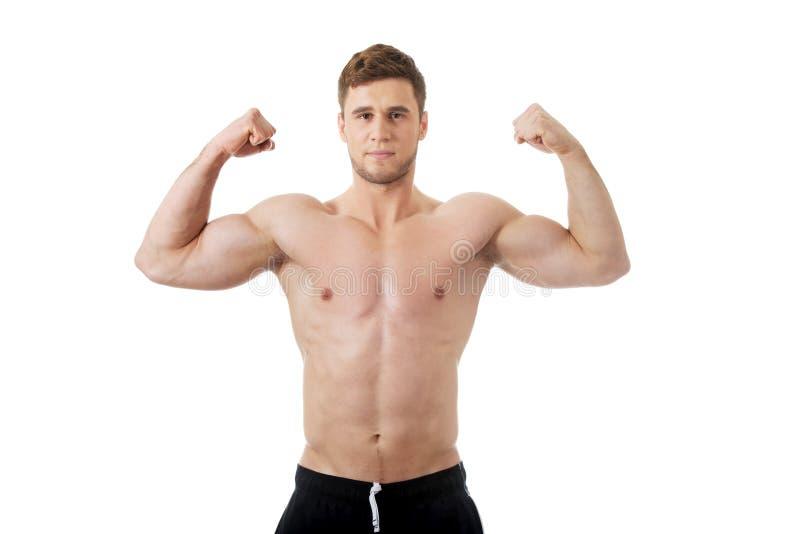Молодой атлетический человек показывая его мышцы стоковая фотография