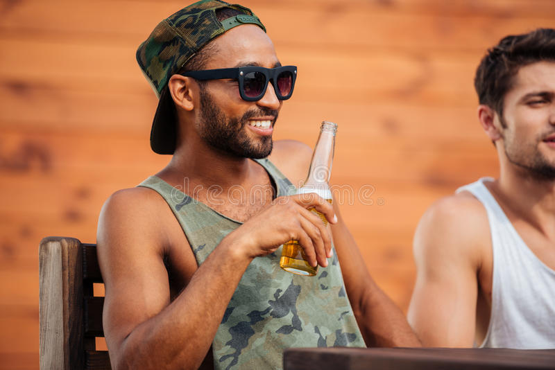 Молодой африканский человек держа пивную бутылку и имея потеху стоковое фото rf