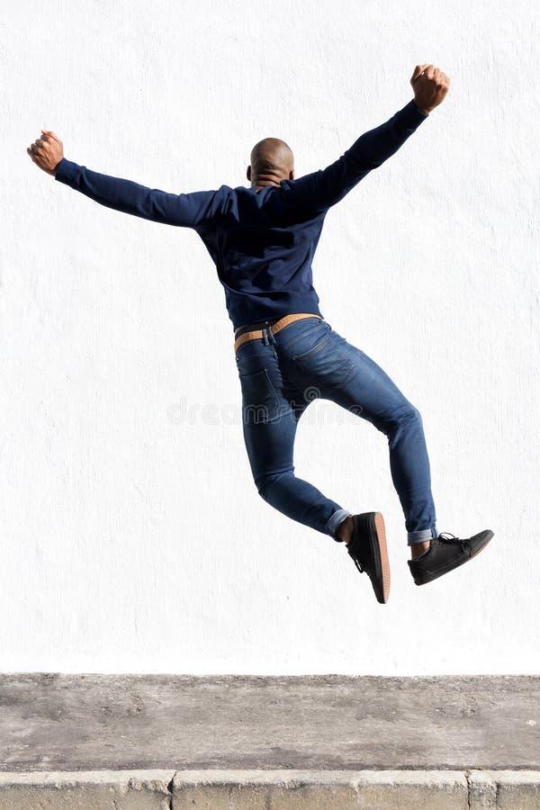 Молодой африканский человек скача в воздух на тротуаре outdoors стоковые изображения
