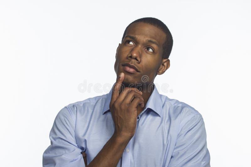 Молодой афроамериканец думая и смотря вверх, горизонтальный стоковые изображения rf