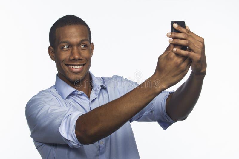 Молодой афроамериканец фотографируя selfie с smartphone, горизонтальным стоковое изображение