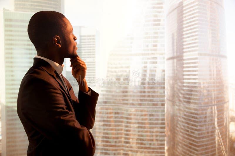 Молодой Афро-американский заботливый бизнесмен смотря через wi стоковая фотография rf