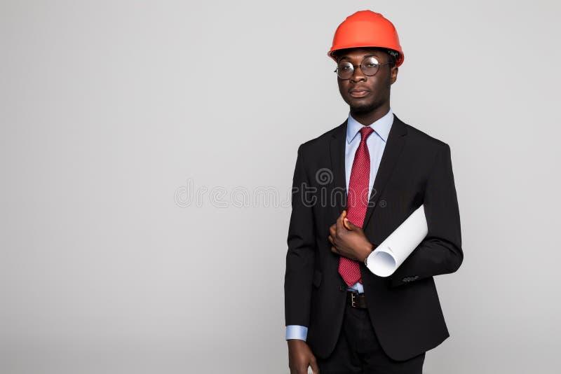 Молодой Афро-американский инженер с светокопиями на белой предпосылке стоковое изображение rf