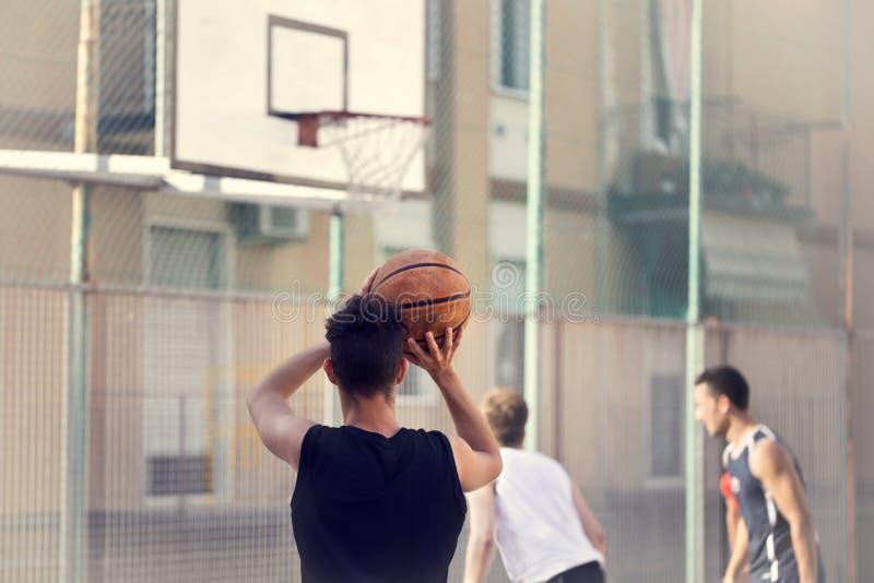Молодой баскетболист готовый для того чтобы снять стоковое изображение rf