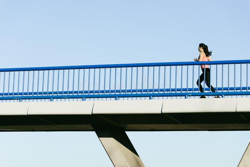 Молодой бегун женщины фитнеса бежать на мосте города стоковое изображение